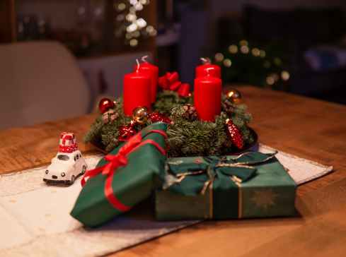 unlighted red advent candles on table beside green gift boxes