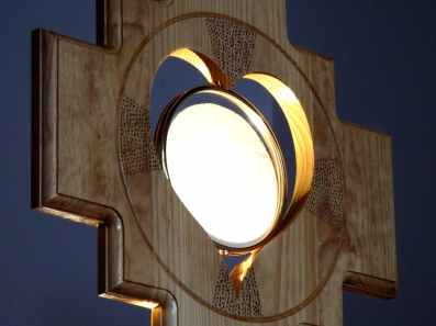 wooden ostensory with lit up sacramental bread in center