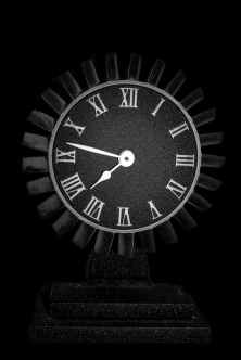round black wooden analog table clock on black surface