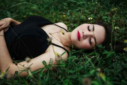 stylish woman with bright makeup resting on lawn