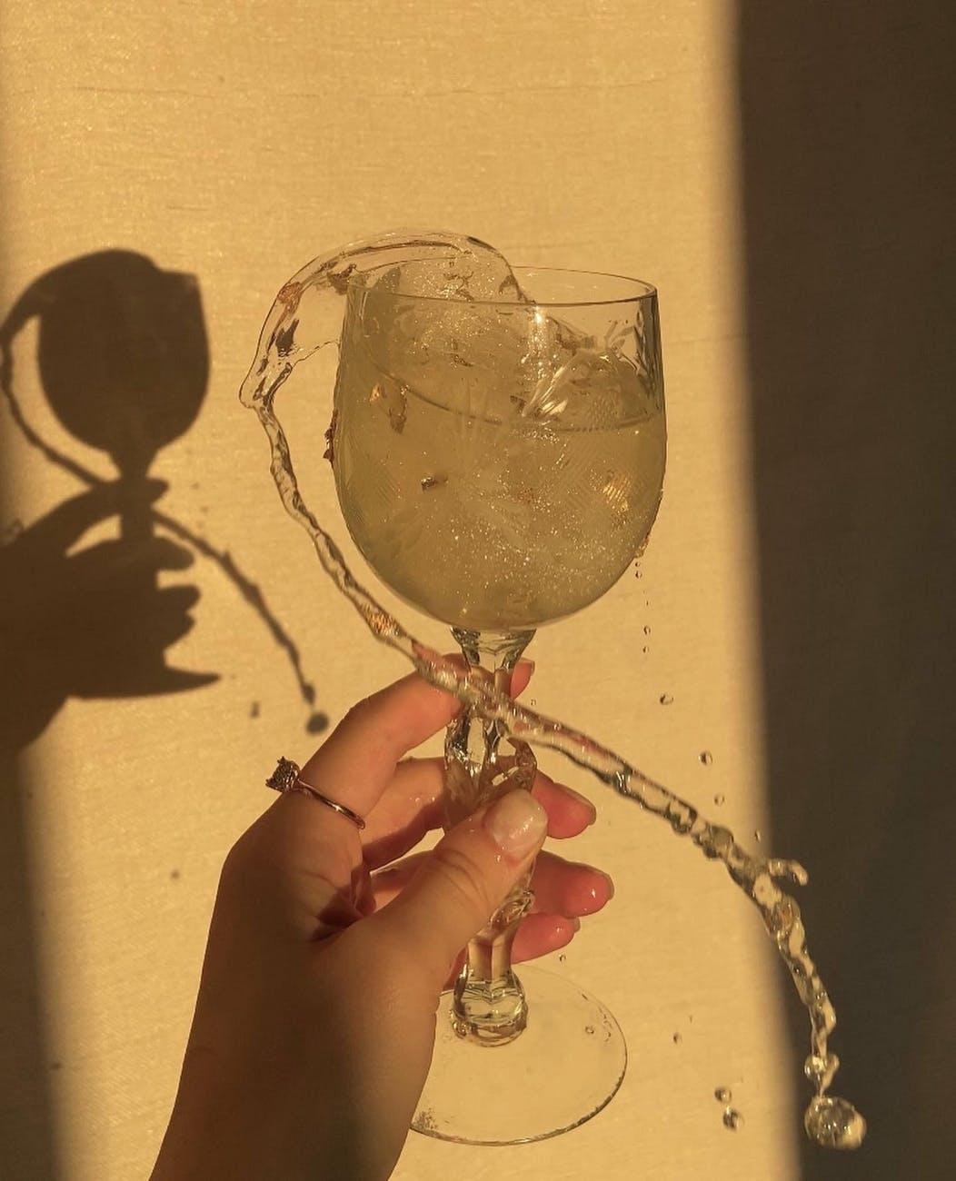 crop woman with splashing drink